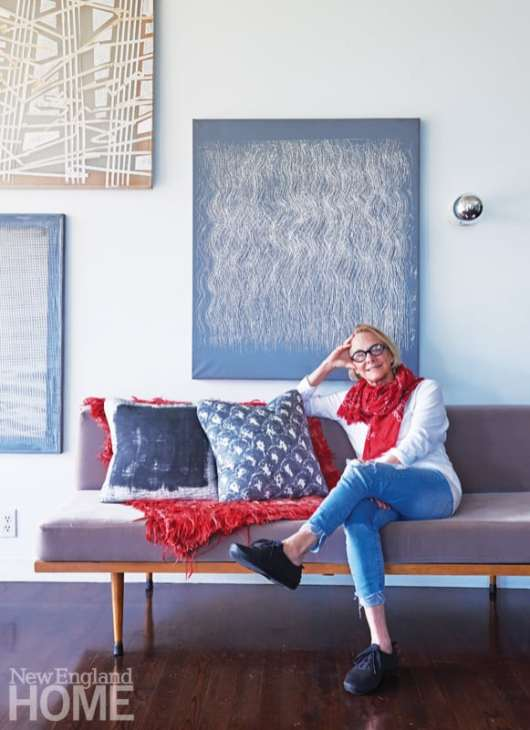 Homeowner Kathleen Tillett relaxes on a vintage Danish bench beneath paintings by her late father-in-law, Leslie Tillett.