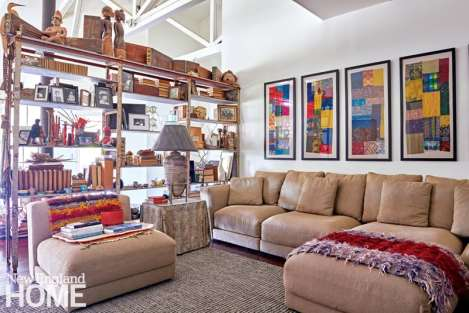 A rusted metal shelf loaded with family mementos serves as a semitransparent room divider.