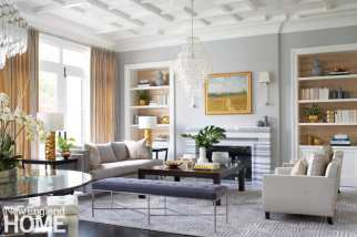 The pattern on the rug that defines the living room area echoes the interlocking squares on the ceiling. A glass chandelier and crystal sconces make elegant companions to the glossy Striato Olimpico marble of the fireplace.