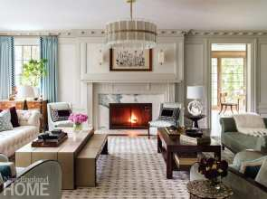 """Farmer divided the living room into two seating groups to help fill its thirty-two-foot length and preserve views of the fireplace from the entry hall. The nesting coffee table can expand to fill the void and provide a game area for the children. """"We didn't want huge coffee tables that you had to circulate around at a party,"""" the designer says."""