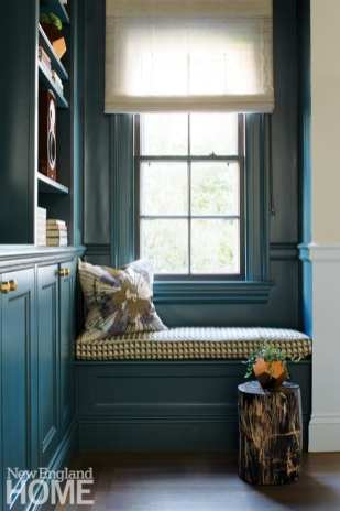 Irving brought the dramatic color into the family room, too, coating the bookshelves and window seat as a contrast to the room's paler walls.