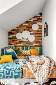 Reading nook featuring blue, orange, rainbow stripes and white cushions, and a wood-paneled wall