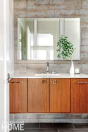 Wood bathroom vanity with white countertop and mirror hanging above