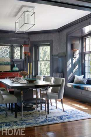 Dining room with table, window seat on the right, and a blue and white rug on top of a wood floor
