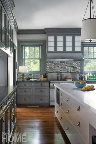 Gray kitchen with leather pulls, a bowl of apples and an arrangement of citrus on the countertop