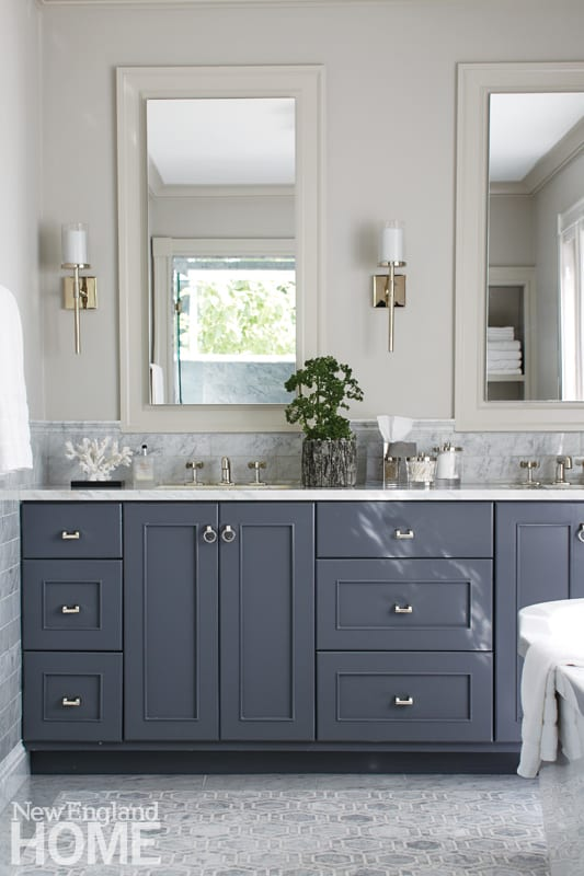 Master bathroom with dark gray vanity, light gray floors, two mirrors over the double sink and off-white walls