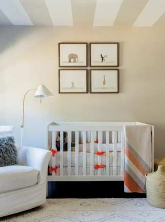Children's nursery with a white crib tied with orange bows. Pictures of animals hang above the crib. There's a white chair next to the crib and a floor lamp with a white shade.