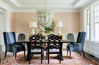 Dining area with large, dark wood table on top of a rug in shades of coral and blue. There's a chandelier above the table that looks like a bunch of clear glass grapes.
