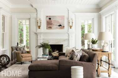 Cozy living room with a brown couch and a wood and marble fireplace