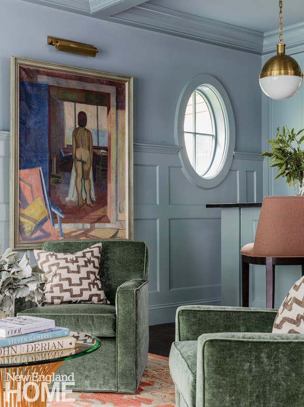 Bar room with gray-blue walls, a painting of a nude woman on the wall, and green armchairs