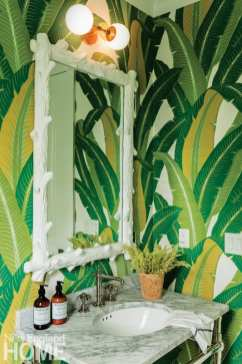 Power room with mirror framed in white fake wood. The wallpaper looks like green fronds.