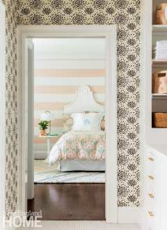 Girl's bedroom as seen through a doorway trimmed in white wood and black and white wallpaper. There's a white bed with a white monogrammed pillow.