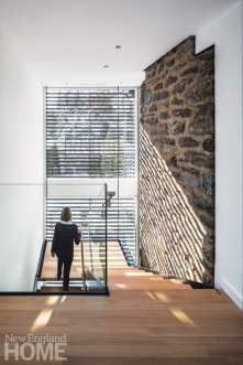 A window wall illuminates the new stairwell, which is anchored on one side by the old exterior chimney.