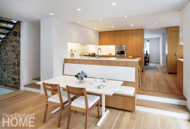 A banquette protrudes from the renovated kitchen, turning part of the circulation spine into a breakfast area.