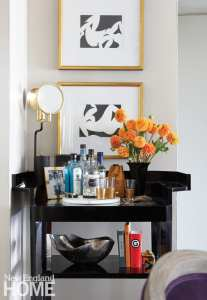 A bar featuring a vase of orange flowers and Matisse-inspired prints.