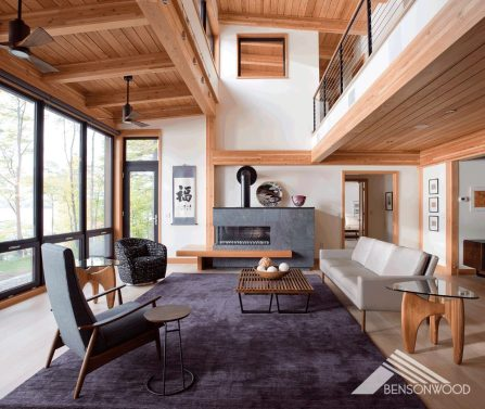 Modern living with high, wood-beamed ceilings, floor-to-ceiling windows and a gas fireplace clad in stone.
