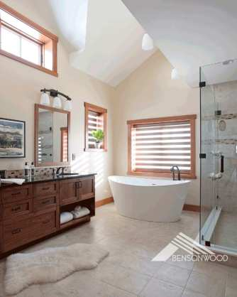 Master bathrooms with dark-wood vanity, large, white, stand-alone bathtub, and a glass shower. There are three wood-framed windows in the room, letting in plenty of natural light.