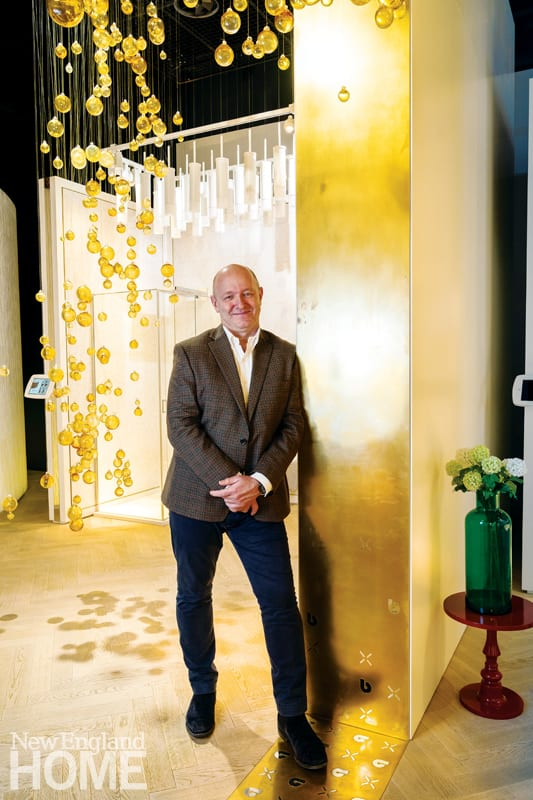 David Hance standing in the showroom of Crosswater London beneath yellow glass globes that hang from the ceiling
