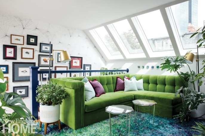 A sitting area featuring a green sectional couch, skylights, white walls, glass hexagonal tables and a shag rug in shades of green, blue and purple.