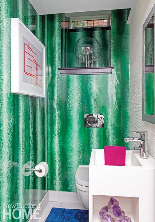 Powder room with white sink, white toilet, wallpaper that mimics malachite and a piece of modern artwork showing pink lines.