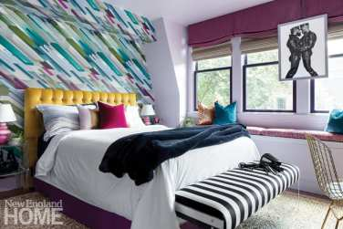 Guest room with a bed featuring a mustard colored headboard, white duvet and a black-and-white striped bench at the foot of the bed. The wallpaper behind the bed is a geometric pattern in shades of purple, blue, green and gray.