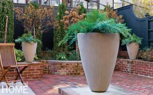 A natural-colored urn with a green plant in it. It's on a table and behind it are brick planters and green foilage.