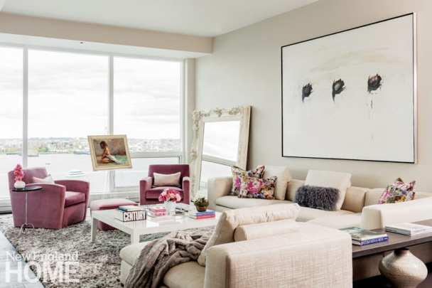 A broader view of the living room featuring the view, a neutral colored couch and a large painting with a white background and black rosebuds hanging above the couch.