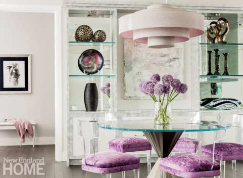 Display case in the dining room near the glass dining room table surrounded by chairs with purple cushions.