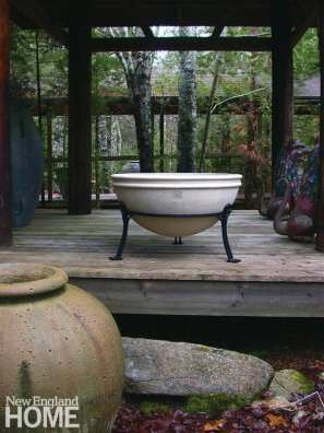 A bowl-shaped planter displayed in a black iron stand on a deck surrounded by forest
