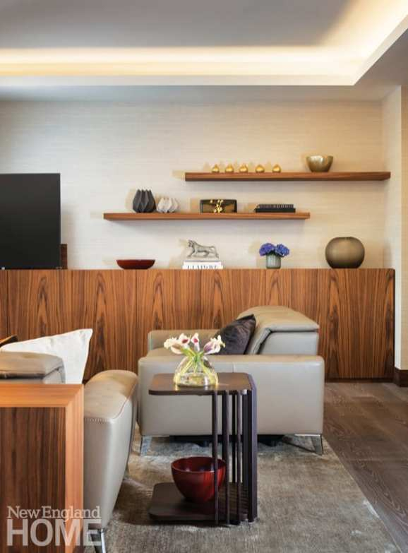 Living area featuring walnut shelving, leather taupe chairs and decorative objects in metallic shades