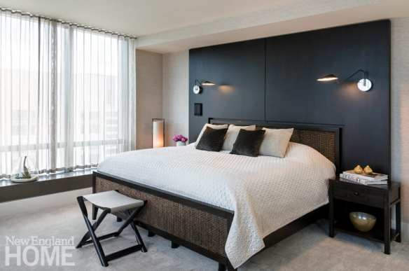 Master bedroom with large bed in front of charcoal gray wall. The bed is clad in beige. There's a stool at the end of the bed.