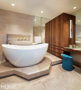 Master bathroom with an oversized white tub. The only color in the room is a blue seat at the vanity.