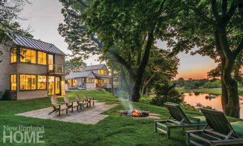 The back of the cottage featuring an expansive green lawn in front of a river. There are Adirondack chairs facing the river and surrounding a fire pit plus two chaise lounge chairs facing the river