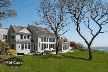 Mid-Cape Home Centers Exterior of two story gray house with expansive green lawn and the ocean in the background