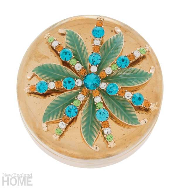 Looking down on a round box that is topped with palm tree leaves