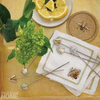 White napkins embroidered with bees and bejeweled cocktail picks featuring ladybugs