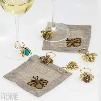 Natural-colored cocktail napkins surrounded by gold wine charms in the shape of bees and other flying insects