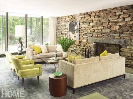 Living room with a stone fireplace, floor-to-ceiling windows, two tan couches, two lime green accent chairs, and walnut tables.