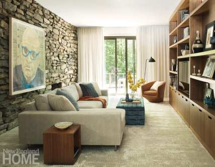 Living room with a stone wall featuring the painting of a bald man in blue glasses. There is a built-in entertainment unit.