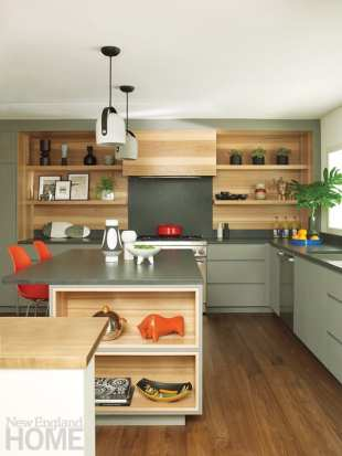 Kitchen with various shades of gray on the cabinets and countertops. The accessories and barstools are orange.