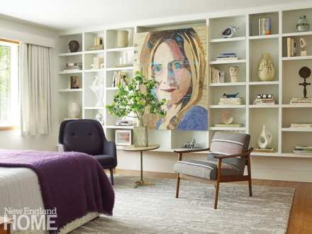 Bedroom with built-shelves filled with sculptures and books. There's a painting of Samantha Bee hanging between the shelves. There are chairs in front of the shelves.