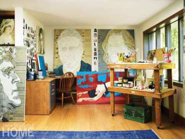 An artist's studio with several paintings in progress and a shelf filled with paints