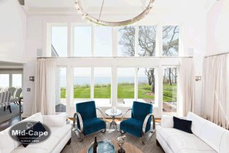 Mid-Cape Home Centers a sitting area with floor to ceiling windows with an ocean view and two blue sidechairs