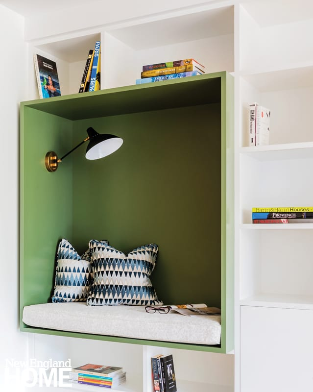 A white wall of built-in shelves with a large green shelf that has been turned into a reading nook complete with a reading light, accent pillows and a white cushion
