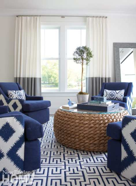 Living room with a round table surrounded by blue and white chairs. There's a blue and white rug on the floor.