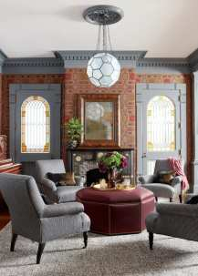 Living room with gray walls and salvaged brown and red wallpaper. There's a small fireplace and four gray houndstooth chairs surrounding a burgundy ottoman being used as a coffee table