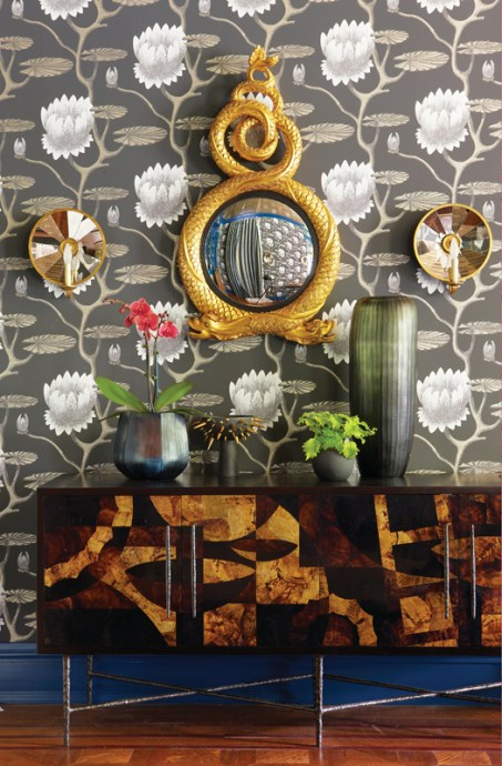 a buffet table in various woods sits in front of a wall with lotus-patterned wallpaper. There's a gold-framed mirror hanging on the wall.