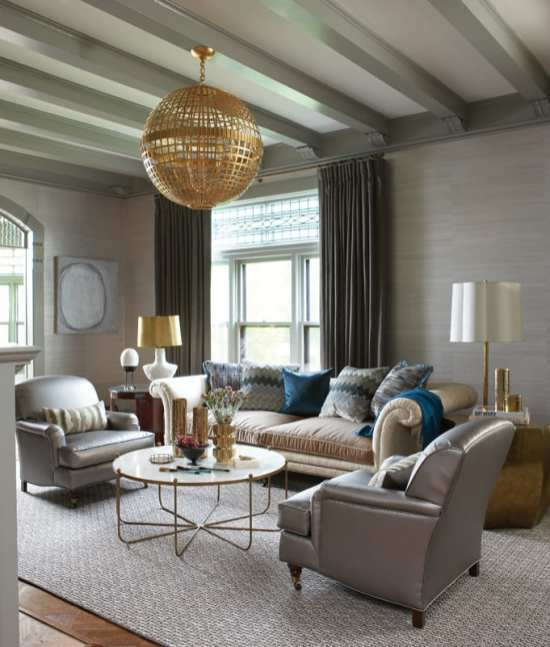 A sitting room with wood-beamed ceilings. The beams are painted gray. The furniture is grays and beiges with some metallic accents.