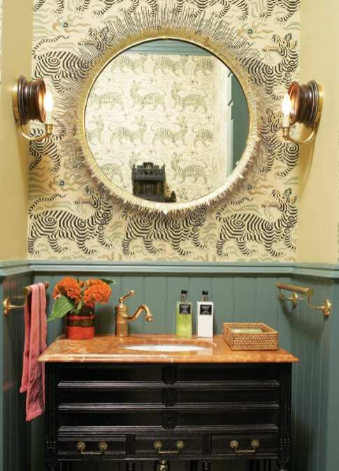 The marble topped sink of a power room with a black vanity and wallpaper with a Chinese tiger pattern