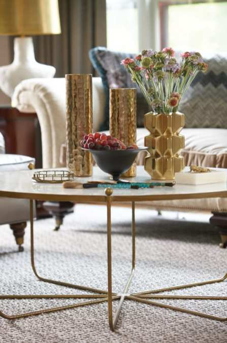 A detail shot of a brass coffee table adored with brass vases.